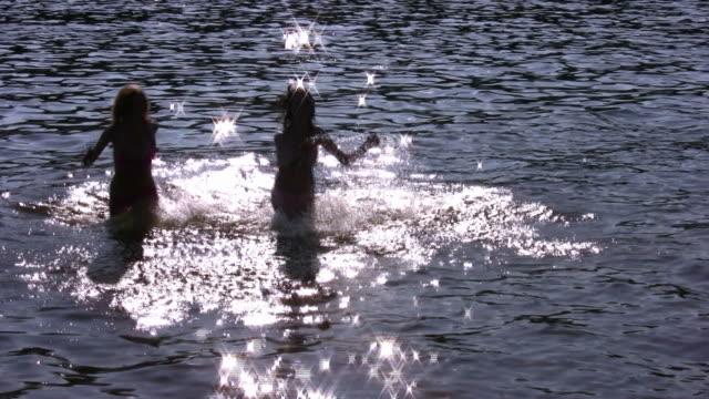 Running girls silhouette in water video