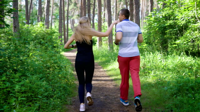 Running in the park. Male and female runners. Sport and healthy lifestyle video