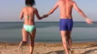 running swimming couple on beach video