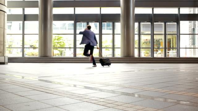 Rushing Business Man Running Through a Japanese Office Lobby video