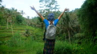 Russian female traveler dressed in casual blue clothing is standing in the middle of Indonesian endless fields, rising her hands and enjoying luxuriant tropical vegetation and fresh air around video