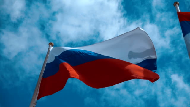 Russian flag on the flagpole waving in the wind against a blue sky with clouds video