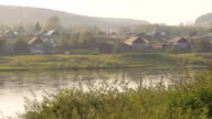 Russian wood village situated on banks of river in morning sun video