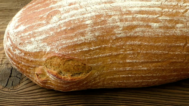 Rustic bread on an old vintage planked wood table. Freshly baked bread in rustic setting on wooden background video