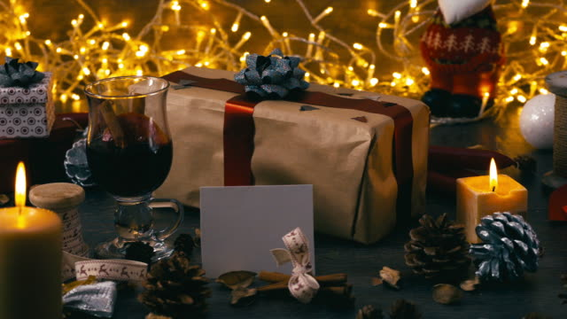 Rustic wooden table with Christmas decorations. Present with blank greeting card. Steady locked down shot. video