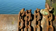 Rusty iron chains beside a lake. video