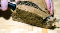 Rye-wheat bread is cut with a knife on a board video