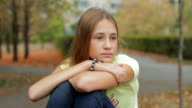 Sad And Depressed Teen Girl Sitting In Autumn Park video