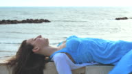 sad and depressed woman lying on a wall by the sea on a windy day video