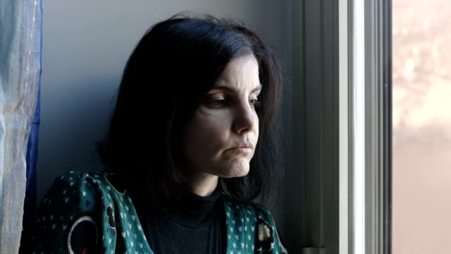 sad and depressed woman near the window video