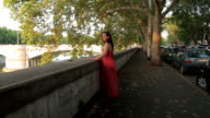 sad and pensive girl with red dress at sunset - steadycam video