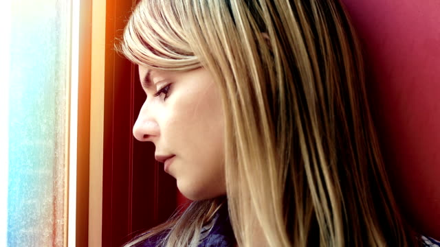sad and pensive woman near the window: depression, thoughtful video