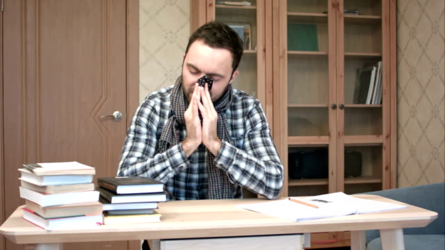 Sad and sick student getting down with flu sitting at the desk with books video