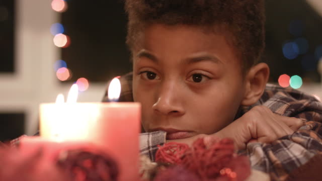 Sad boy looking at candle. video