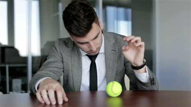 Sad businessman meditates looking on the spinning ball. video
