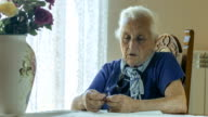 Sad elderly woman praying with a rosary in hand, cross video