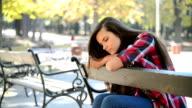 Sad girl sitting on a bench video