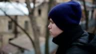 Sad homeless teenager sitting alone, looking into camera, social advertising video