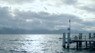 Sad landscape, rough water surface, stormy cloudscape over mountains on horizon video