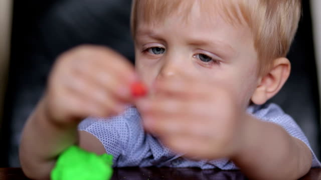 Sad little boy playing with colorful plasticine. video