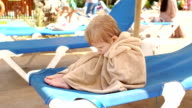 Sad little boy sitting on the loungers on beach. video
