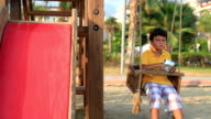 Sad lonely boy eating chips on swing video