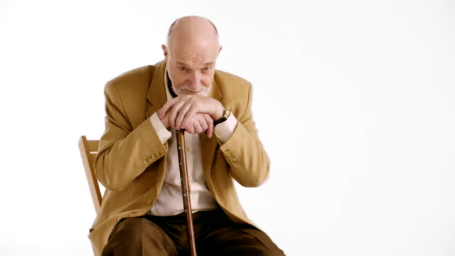 Sad lonely old man with piercing eyes sitting in an armchair with his cane video