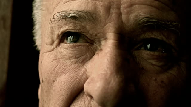 sad lonely old man's eyes in front of the window video