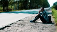Sad man sit at road in countryside. Hitchhiking. Waiting. Smoking cigarette video