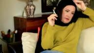 Sad muslim woman smoking cigarette video