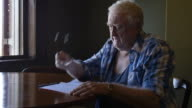 Sad old elderly man in retirment pondering letter at table video