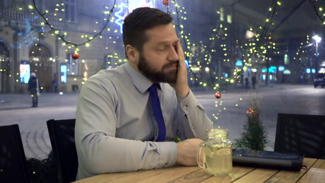 Sad pensive businessman drinking hot warming drink, night, in cafe, christmas video
