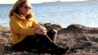 Sad pensive woman on winter sea beach video