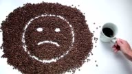 Sad smiley made of coffee beans becoming happy video