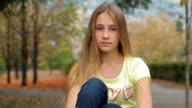 Sad Teenage Girl Portrait Looking At Camera In Autumn Park video