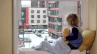 Sad toddler boy with best friend teddy bear looking at snow fall through window video
