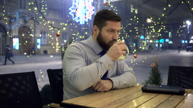 Sad troubled businessman drinking hot warming drink, at night, in cafe video