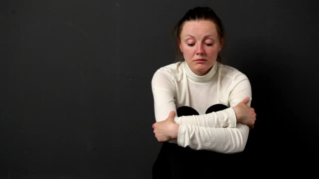 Sad woman is sitting on the floor near the gray wall enfolding the knees by the hands, she is looking as a victim of a domestic violence video