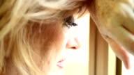 Sad woman near window thinking about something video