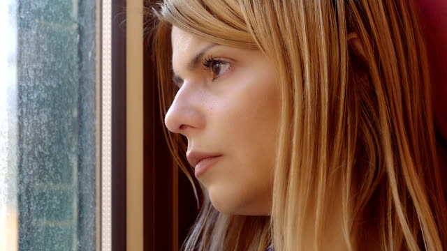 sad woman portrait: depressed young woman looking out of the window video