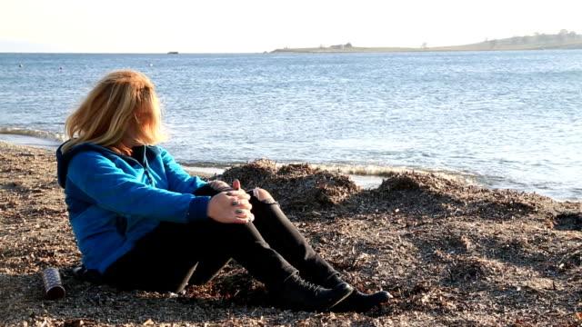 Sad woman sitting at the seaside video