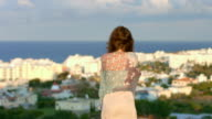 Sad woman wrapped in scarf looks at seaside town, amazing video