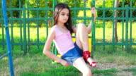 Sad young girl on swings video