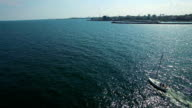 Sailboat at sea and coastline, aerial flight video