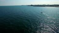 Sailboat at sea and coastline, aerial view video