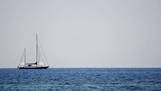 Sailboat in regatta on blue sea water surface horizon video