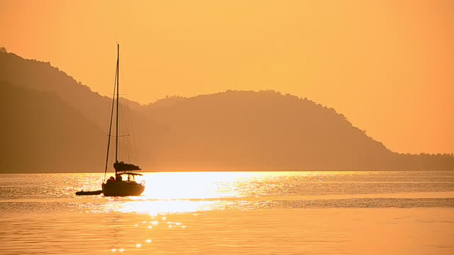 Sailboat on tropical sunset beach video