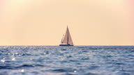 SLO MO Sailboat sailing on the horizon at sunset video