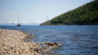 A sailing boat moves away from pebbly shore in background of a chain of mountains and steep forest video