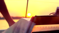 sailing into the sunset on blurred reflected water with bokeh video